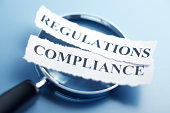 "The words ""Compliance"" and ""Regulations"" are printed on a torn pieces of paper that sit on top of a magnifying glass which sits on a blue background. The image is created using a very shallow depth of"