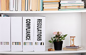 Compliance and Regulations concept. document folders and organizers, white book shelf