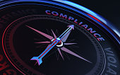 Arrow of a compass is pointing compliance text on the compass. Arrow, compliance text and the frame of compass are metallic blue in color. Red light illuminating compass is creating a sense of tension