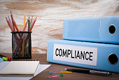 Compliance, Office Binder on Wooden Desk. On the table colored pencils, pen, notebook paper