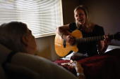Complimentary therapies manager Jen Dunlap sings during a music therapy session for terminally ill hospice resident Evelyn Breuning at the Hospice of...