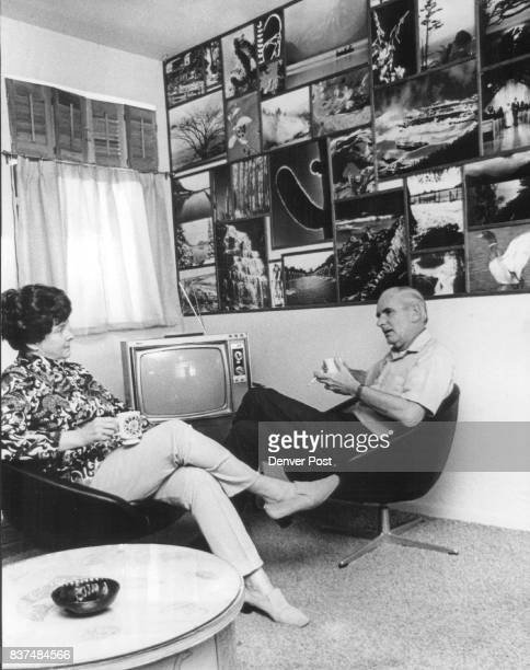 Composer and her husband rest in den in front of Demarest's photo wall that served as an inspiration center and a memory jogger in devising subtitles...