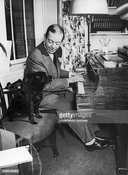 Composer Cole Porter playing the piano with his dog on a chair beside him circa 1956