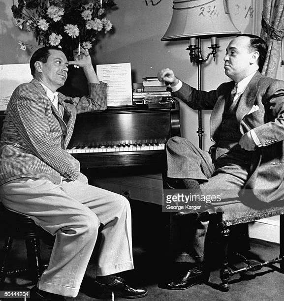 Composer Cole Porter sitting at piano chatting w unident friend while staying in the Ritz Hotel during outoftown tryouts for his new Broadwaybound...