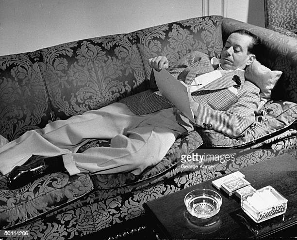 Composer Cole Porter writing music as he reclines on couch in the Ritz Hotel during outoftown tryouts of his new Broadwaybound musical Du Barry Was a...