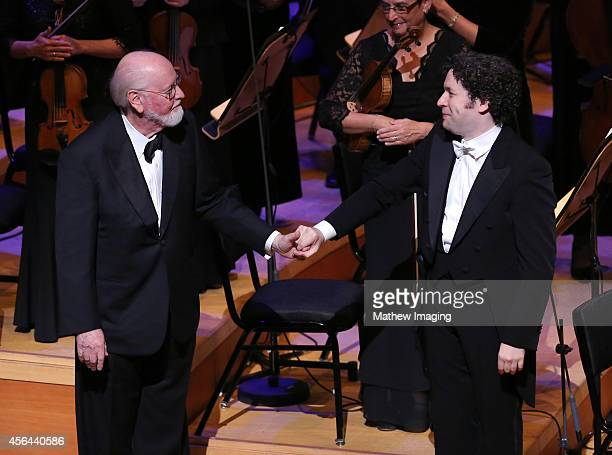 Composer John Williams and conductor Gustavo Dudamel shake hands onstage at Los Angeles Philharmonic's Walt Disney Concert Hall Opening Night Gala on...