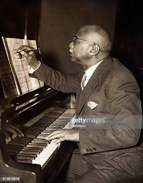 Composer WC Handy makes notations on sheet music while creating St Louis Blues