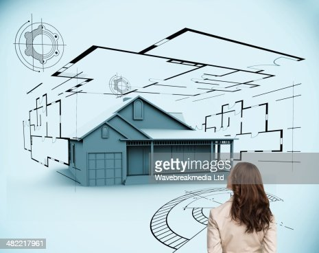 Brunette businesswoman looking at 3d house : Stock-Foto