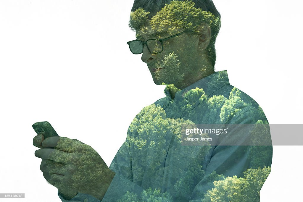 composite image of man using mobile phone and tree : Stock Photo