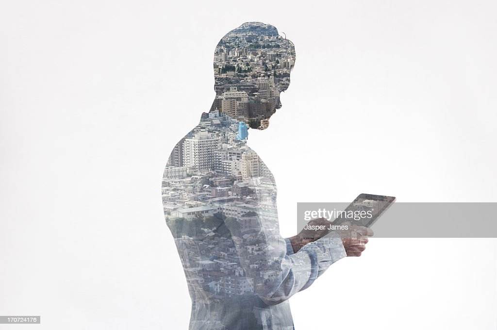 composite of businessman using ipad and cityscape