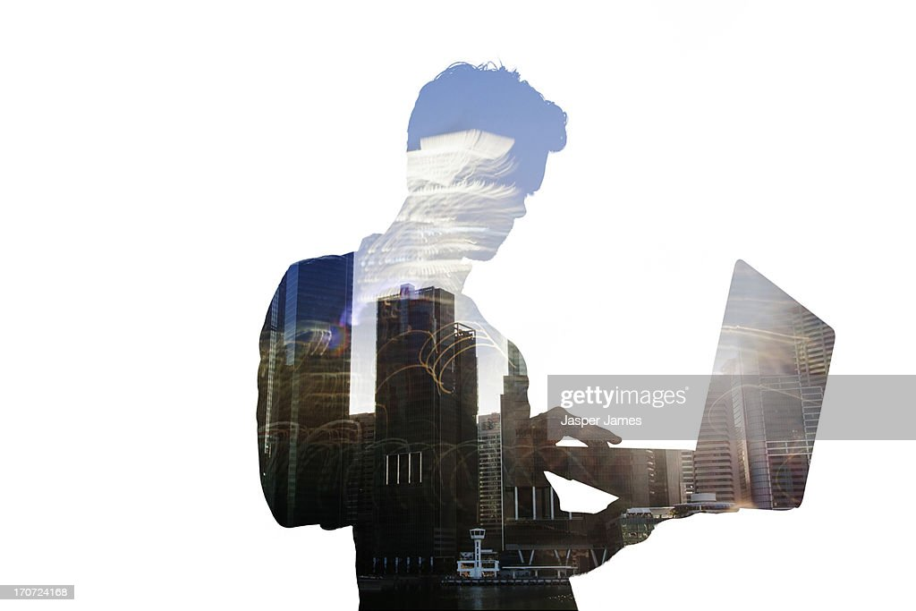 composite of man using laptop and cityscape : Stock Photo