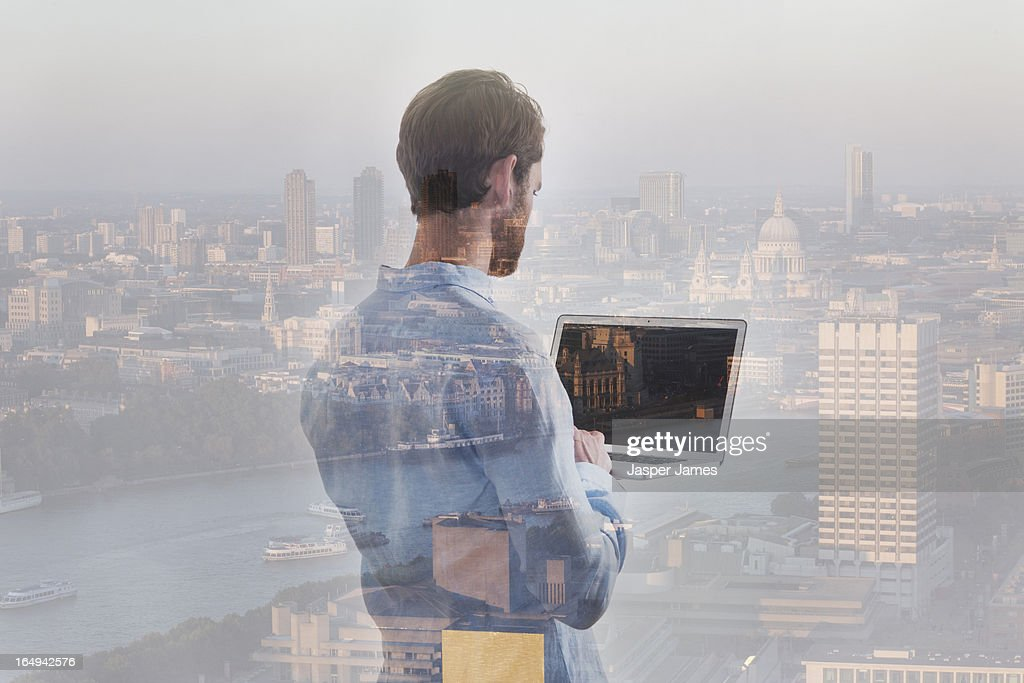 composite of man using laptop and london cityscape : Stock Photo