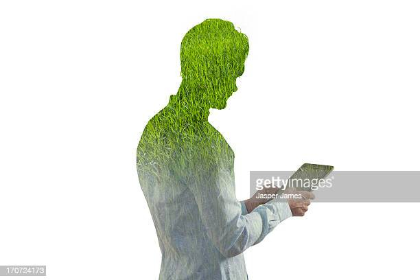 composite of man using ipad and green grass