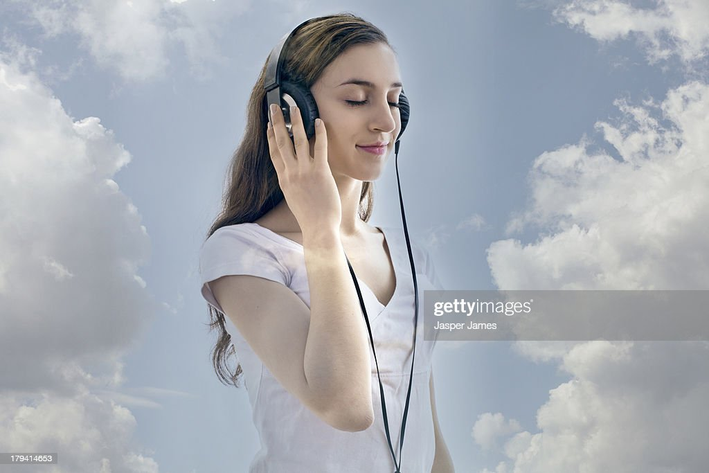 composite of woman listening to headphones and sky : Stock Photo
