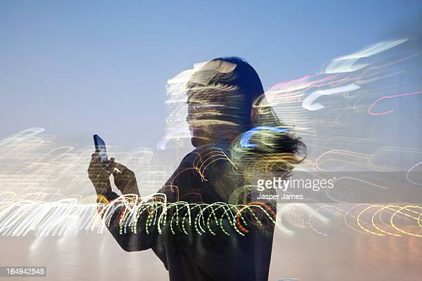 composite of woman texting on phone and cityscape