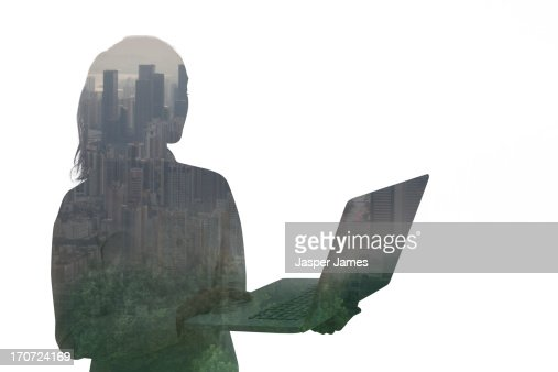 composite of young woman using laptop and cityscap : Stock Photo
