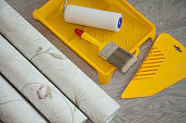 Composition tools for home repair and interior renovation indoors. Rolls of wallpaper, roller and glue container on wooden surface