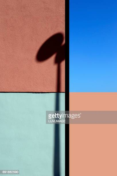 Composition with a painted wall, blue sky and abstract shadow.