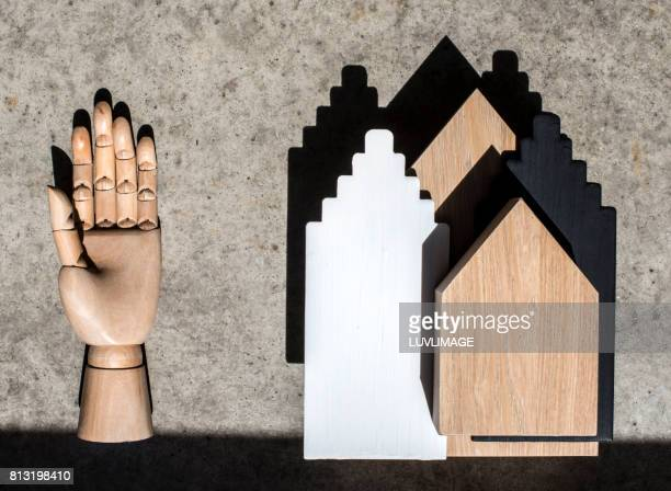 Composition with a wooden hand and miniature houses.