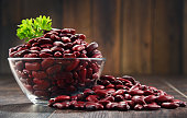 Composition with bowl of kidney bean on wooden table.
