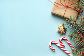 Christmas background. Composition with Christmas gift box, fir tree branch, candy canes and decorations on blue background. Top view with copy space.