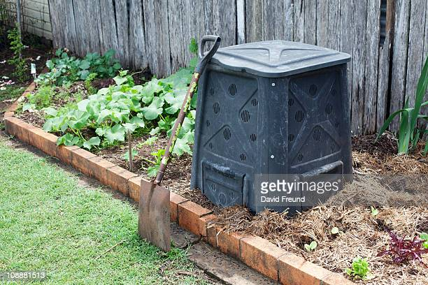 Compost bin in a backyard vegetable garden.
