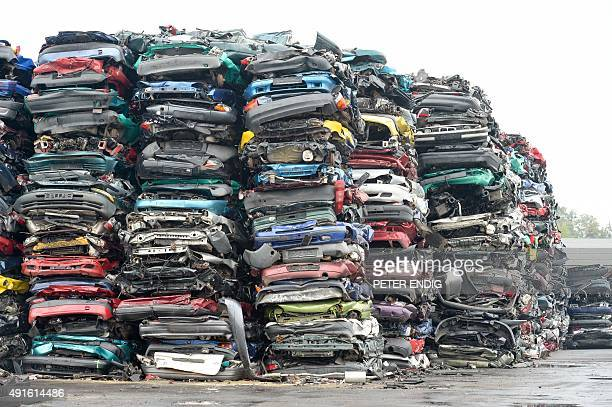 Compressed cars piled up in freightfriendly bales of scrap await their transport on October 6 2015 on the grounds of a car recycling company in...