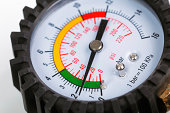 A compressor pressure gauge on a white background