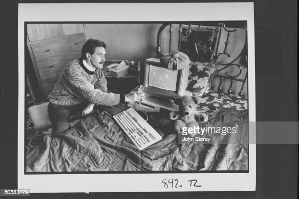 Computer analyst John McAfee holding stethoscope to IBM type computer sitting on bed w ice bag on top illustrating computer virus which McAfee is...