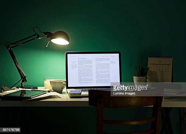 Computer and cell phone illuminated by desk lamp at night