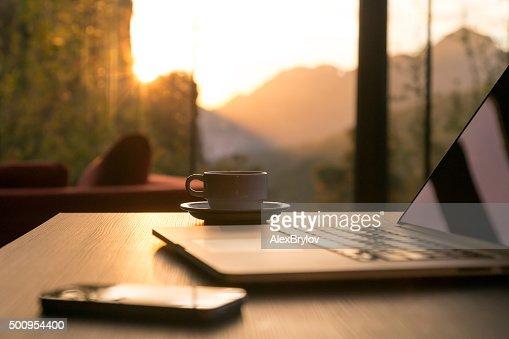 Computer Coffee Mug Telephone on black wood table sun rising : Stock Photo