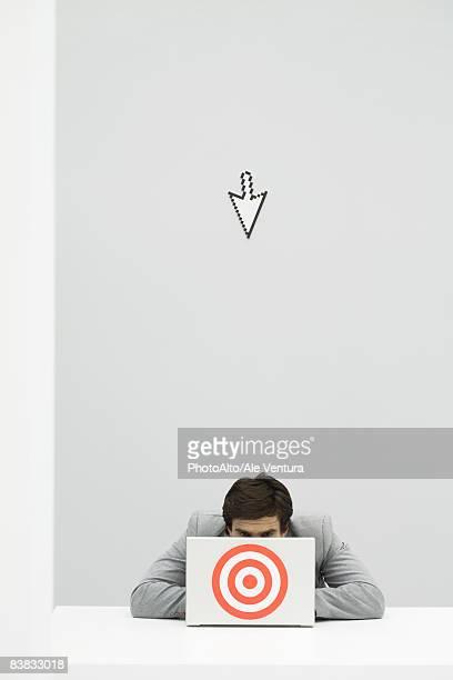 Computer cursor pointing at businessman hiding behind target
