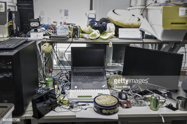 Computer equipment and personal belongings sit on an employee's desk in the research and development department at Bitmain Technologies Ltd's...