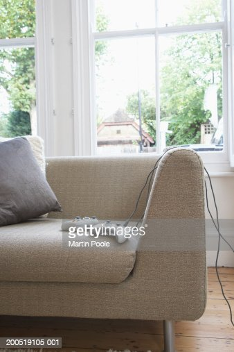 Computer game consols on sofa in living room : Stock Photo
