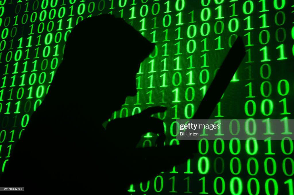Computer hacker silhouette. Green binary code background