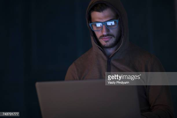 Computer hacker wearing hooded shirt using laptop against wall