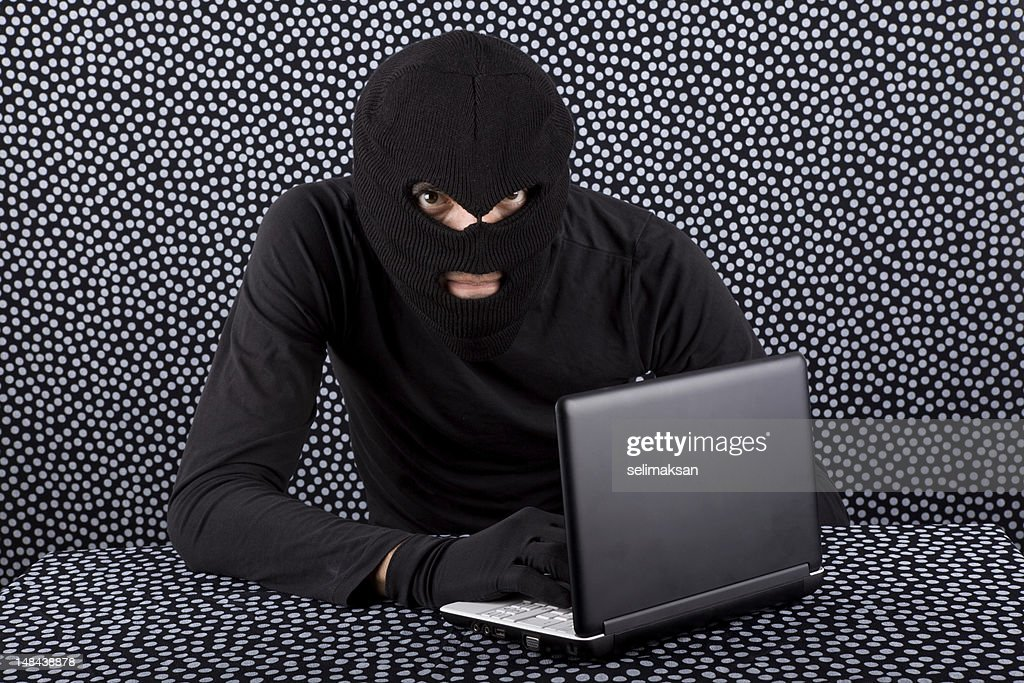 Computer hacker with mask and glove on speckled background : Stock Photo