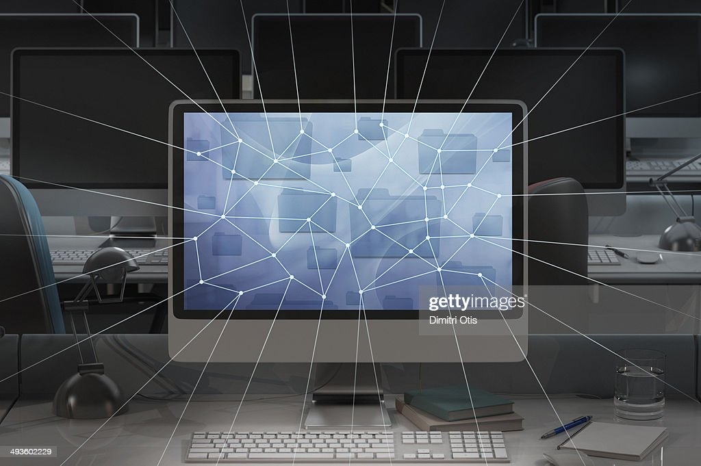 Computer in dark office, network lines radiating
