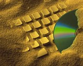 Computer Keyboard and CD-R buried in sand, Close Up, High Angle View