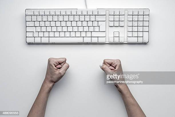Computer keyboard and female clenched fists