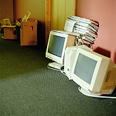 Computer monitors and keyboards on office floor