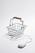Computer mouse connected to shopping basket for online shopping