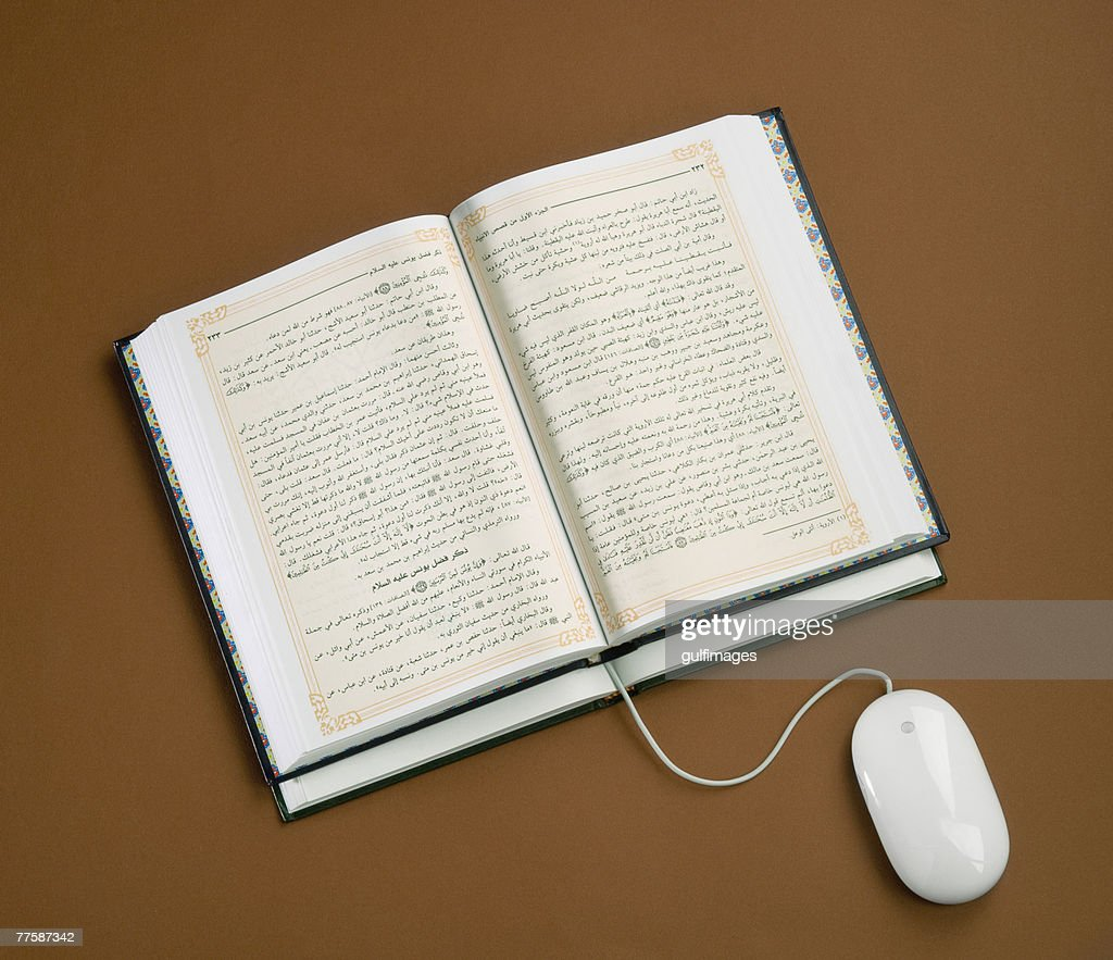 Computer mouse wire used as bookmark in book, close-up, elevated view : Stock Photo