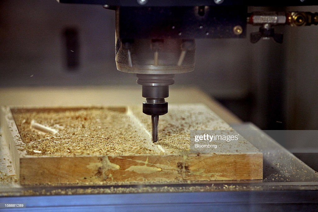 A computer numerical control (CNC) machine mills and cuts a Lakland bass guitar body from a block of wood at the company's production facility in Chicago, Illinois, U.S., on Thursday, Dec. 27, 2012. Manufacturing picked up in December, reflecting growth in orders, employment and exports that indicate the U.S. expansion will be sustained in 2013 following the budget deal. Photographer: Tim Boyle/Bloomberg via Getty Images