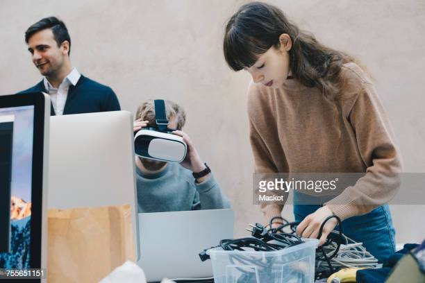 Computer programmer wearing VR glasses while colleagues working in office
