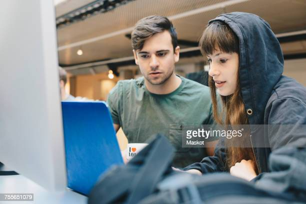 Computer programmers using laptop at office