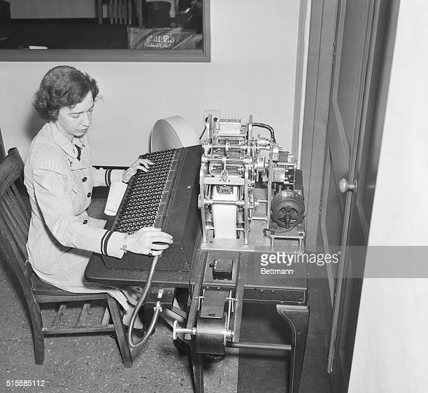 Computer scientist Grace Hopper works on a manual tape punch an early computer