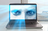 Laptop with staring eyes and binary code