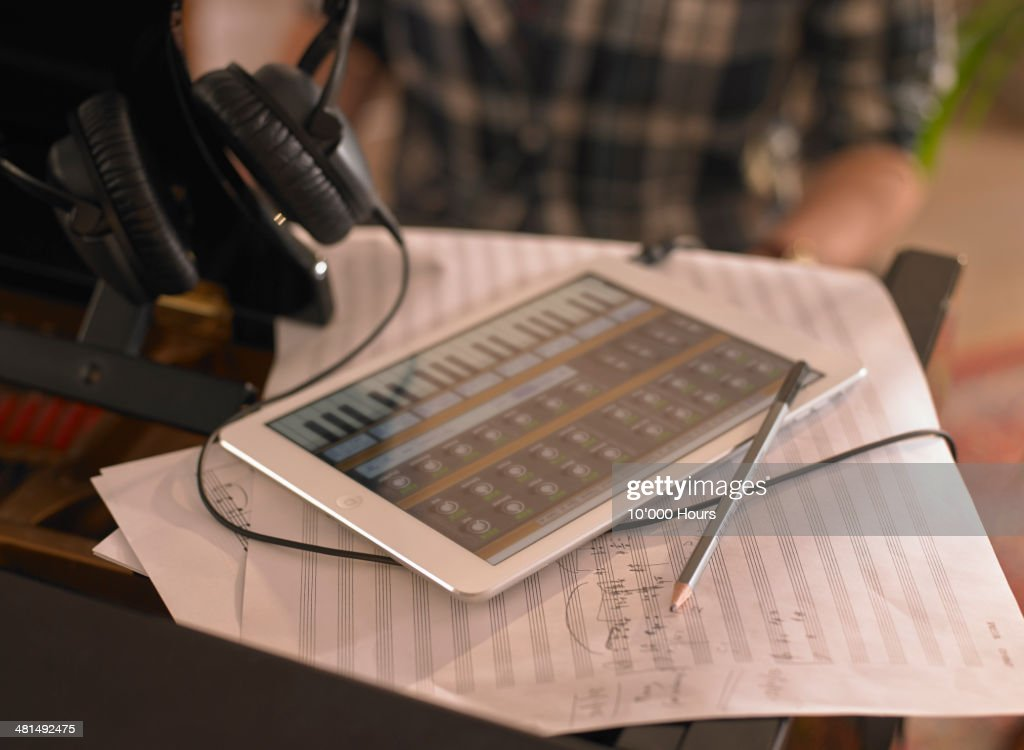 Computer tablet on top of a piano with music app : Stock Photo