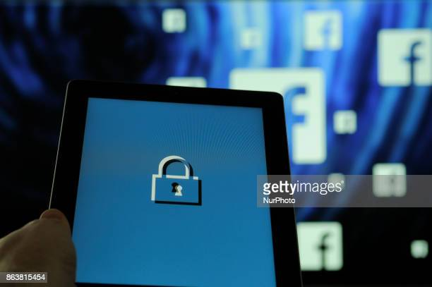 A computer tablet with a security lock symbol with Facebook logos in the background is seen in this photo illustration on October 20 2017